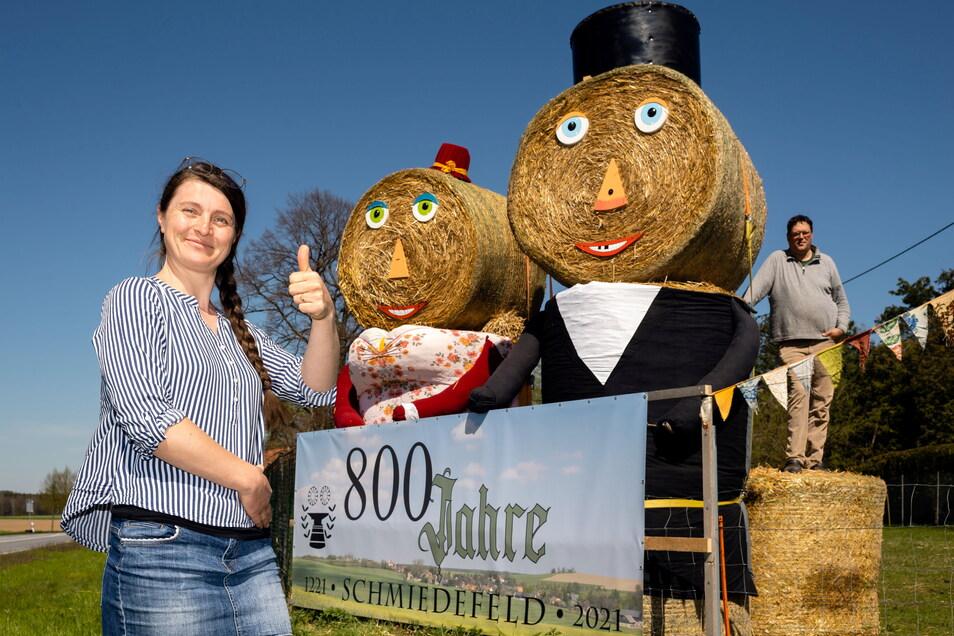 Mit diesen Strohpuppen macht der Ort Schmiedefeld auf sein Jubiläum aufmerksam. Lisette Rarisch vom Kultur- und Sportverein hat die Kleidung für die Puppen genäht. Landwirt Christian Ahrens spendierte das Stroh.