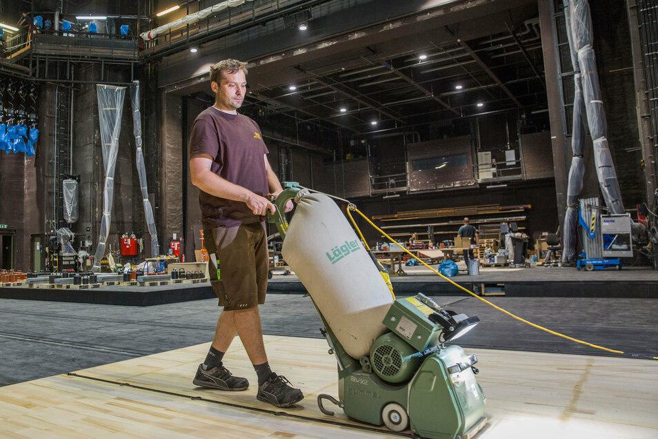 Dirk Lattermann schleift den neu verlegten Schwarzkiefern-Belag auf der Hauptbühne der Semperoper ab. Dort ist nächste Woche bereits die erste Aufführung nach der Sommerpause.