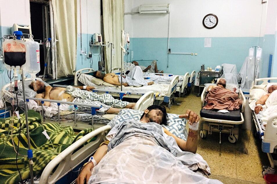Männer, die bei dem tödlichen Anschlag in der Nähe des Flughafens von Kabul verletzt wurden, liegen in einem Krankenhaus.
