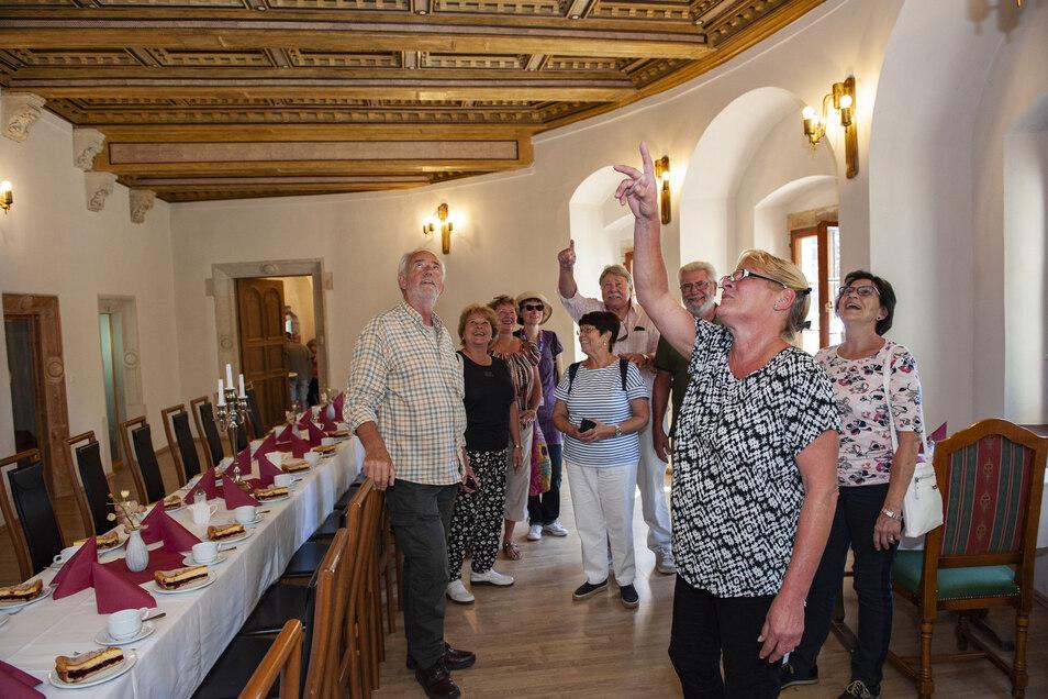 Britta Teichmann (2.v.r.) vom Förderverein erklärt Gästen aus Berlin im Herrenzimmer des Schlosses die kunstvolle Holzdecke. Die Kaffeetafel ist auch schon gedeckt.