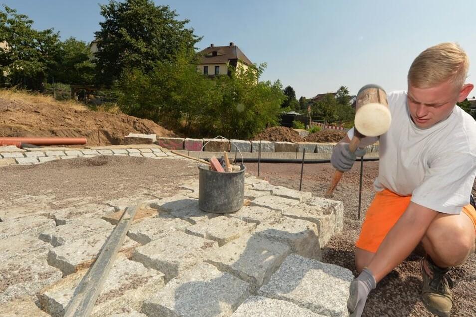 Die Überströmstrecke wird von Lehrling Richard Poeschk mit bis zu 50 Kilogramm schweren Pflastersteinen angelegt.