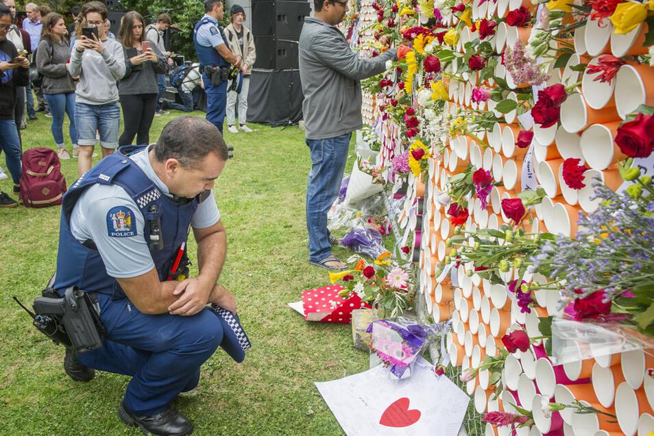 Ein Polizist kniet nieder, um einige der Botschaften zu lesen, die auf einem behelfsmäßigen Denkmal für die Opfer der Anschläge von Christchurch an der University of Canterbury hinterlassen wurden.