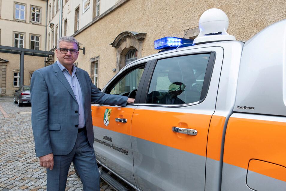Amtsleiter Steffen Klemt zeigt auf dem Hof des Landratsamtes in Pirna einen Dienstwagen des Katastrophenschutzes, der mit einer mobilen Sirene ausgestattet ist.