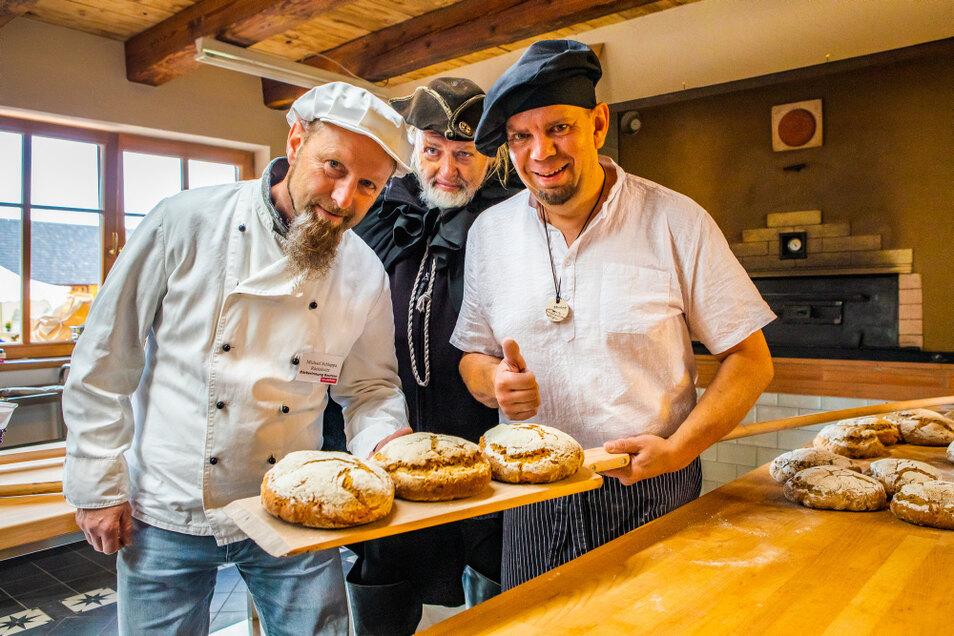Bäckermeister Rico Ziegenbalg (re.) hatte schon Krabat-Mühlen-Brote gebacken, als Bäckermeister Michael Schlappa aus Räckelwitz (li.) im Namen der Bäckerinnung gratulierte. Auch der Schwarze Müller war an diesem Tag dabei.