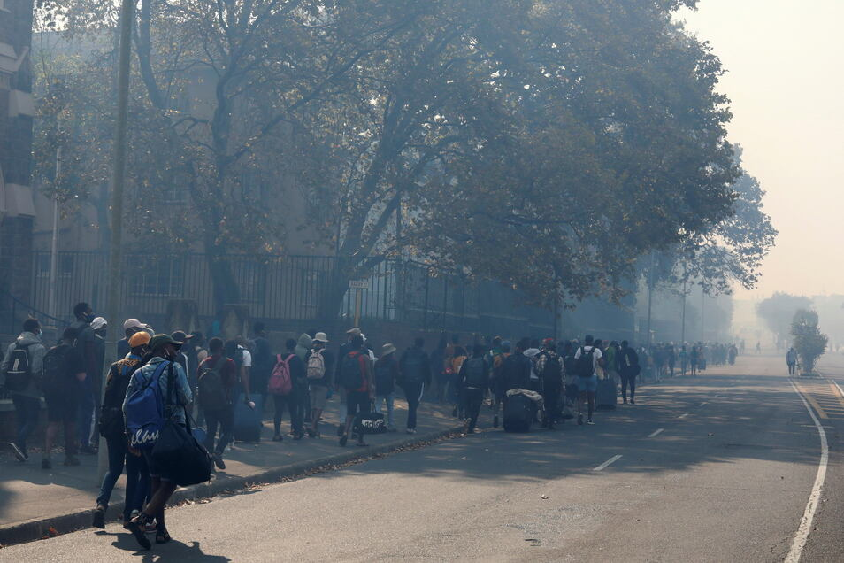Studenten der Universität Kapstadt verlassen ihren Campus, der zuvor aufgrund eines Brandes auf dem Tafelberg evakuiert wurde.