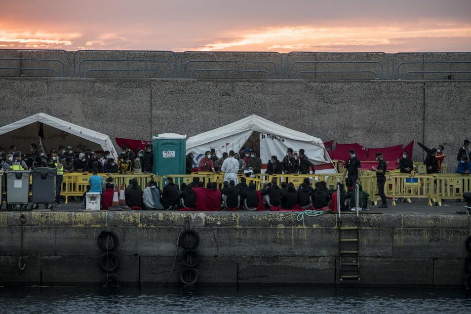 Migranten sitzen im Hafen von Arguineguin auf Gran Canaria nach ihrer Rettung.