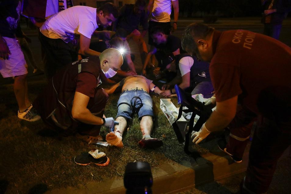 Sanitäter behandeln einen Verletzten nach Zusammenstößen mit einem Polizisten.