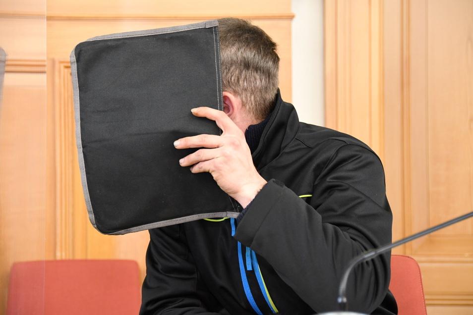 Der angeklagte Weißwasseraner verdeckt sein Gesicht mit einer Mappe