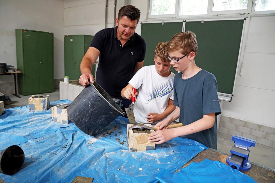 Thomas Möbius hilft Gregor (M.) und Alexander bei den letzten Arbeitsschritten für den eigenen Lampensockel.
