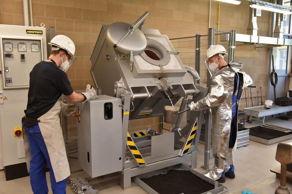 Azubi Richard Alex und Dominik Lohrmann (re.) von der Schmiedeberger Gießerei präsentieren das Gießen von Alu am neuen Ofen.