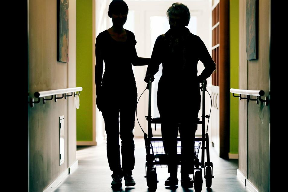 Eine Pflegekraft (l) begleitet die Bewohnerin eines Altenheims mit Rollator. Der Bundestag will 20.000 Hilfspfleger finanzieren.
