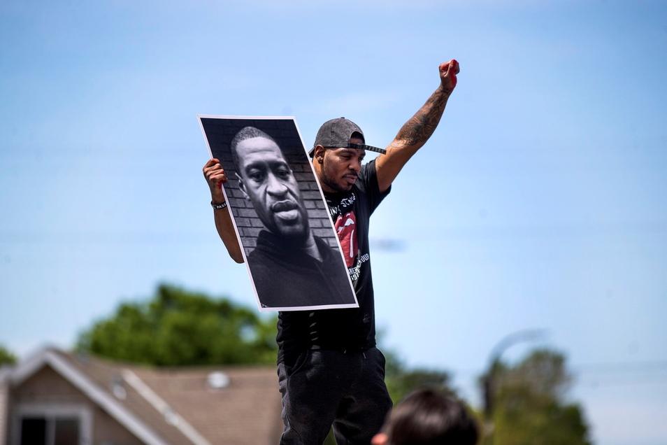 Tony L. Clark hält ein Foto des verstorbenen George Floyd. Gut ein Jahr nach der Tötung des unbewaffneten Afroamerikaners bei einem Polizeieinsatz beginnt in den USA das Hauptverfahren gegen den Hauptangeklagten.