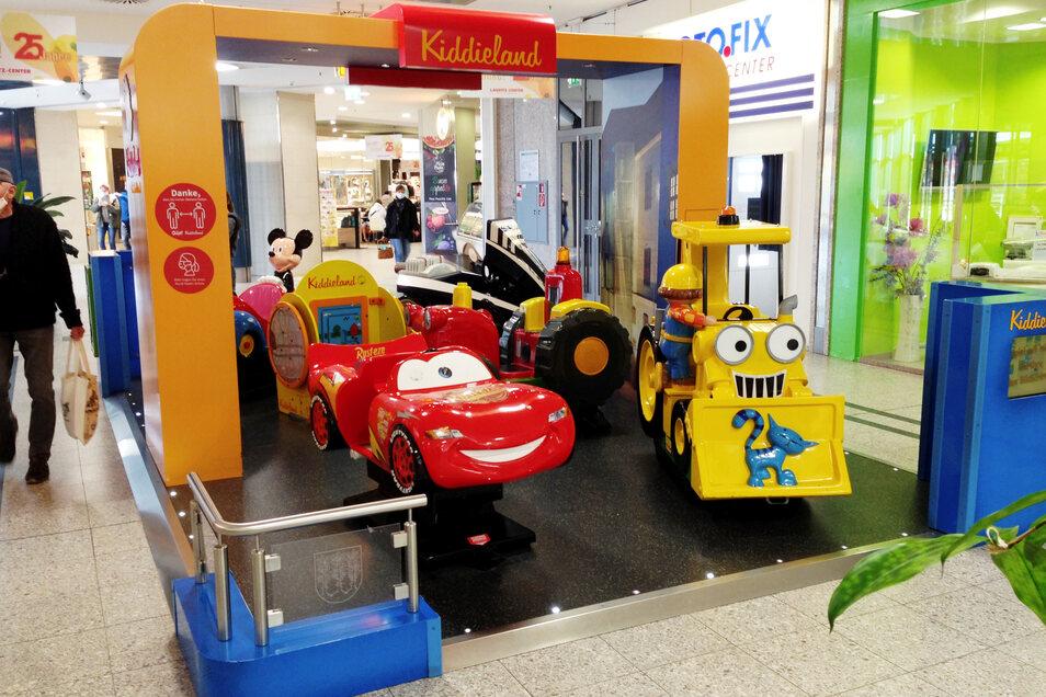 """Das """"Kiddieland"""" im Hoyerswerdaer Lausitz-Center bietet Kindern Spielmöglichkeiten – teils gegen Bezahlung (wie die Benutzung der Mobile); teils auch gratis wie Gedulds- und Konzentrations-Aufgaben. Derweil können die Eltern auf einer Bank plausch"""