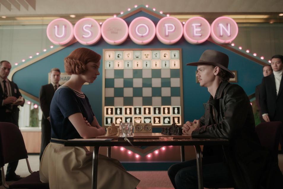 Anya Taylor-Joy als Beth Harmon und Thomas Brodie-Sangster als Benny spielen Schach in der Serie.