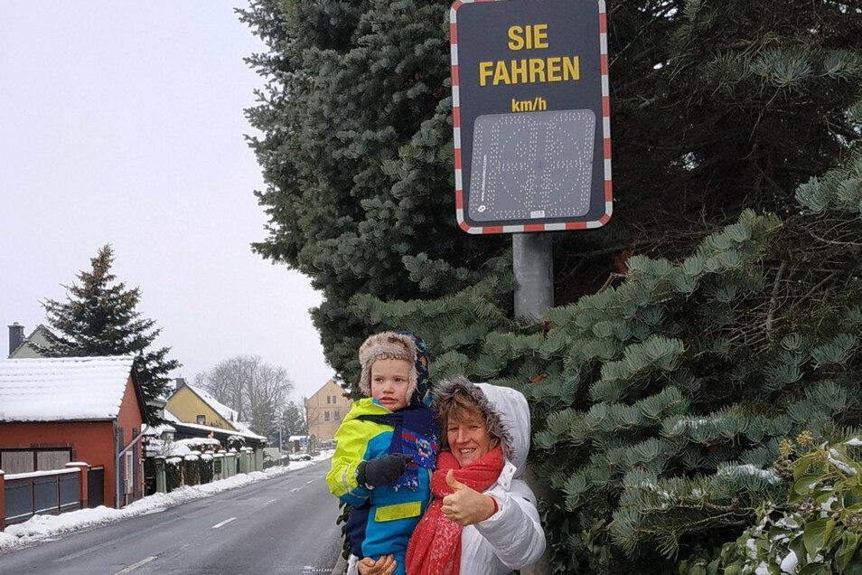 Sylvia Müller aus Oßling freut sich mit ihrem Enkelkind, dass die Geschwindigkeitsanzeigetafel jetzt am Ortseingang steht. Bald kommt noch ein Tempo-30-Schild an die Durchgangsstraße.
