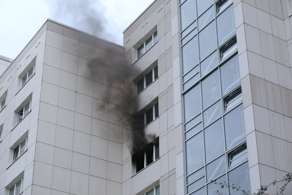 Dunkler Rauch quillt aus dem Fenster der brennenden Wohnung.