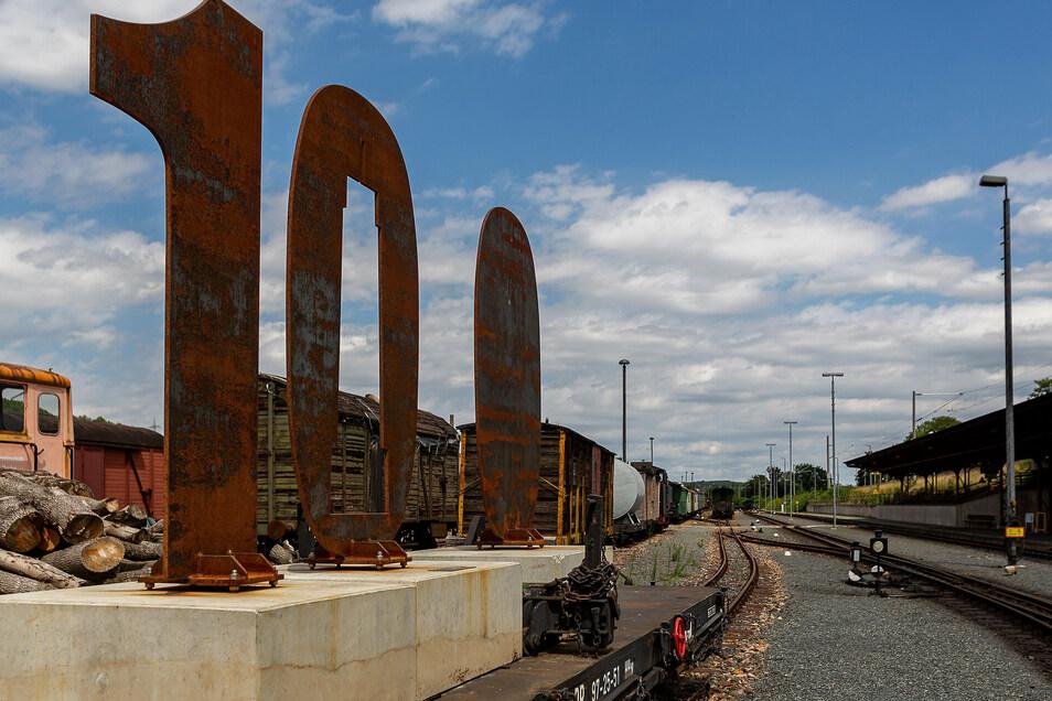 """Die """"100"""" steht zur Zeit auf einem Wagon der Weißeritztalbahn am Bahnhof Hainsberg. Die Stele ist das sichtbarste Zeichen des bevorstehenden Stadtjubiläums."""