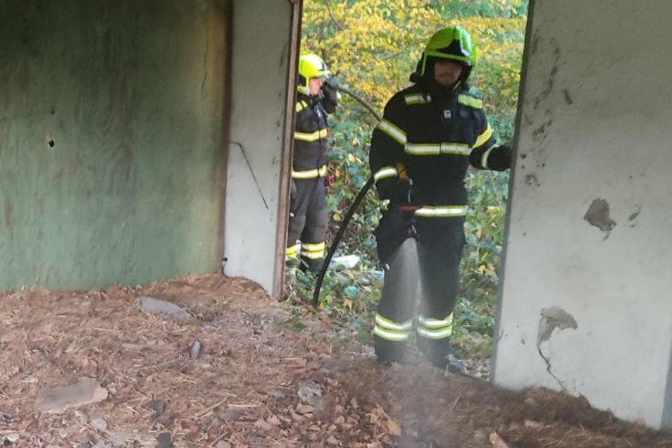 Glaubitzer Feuerwehrmänner löschen einen von drei Brandherden in der Baracke am Wald.