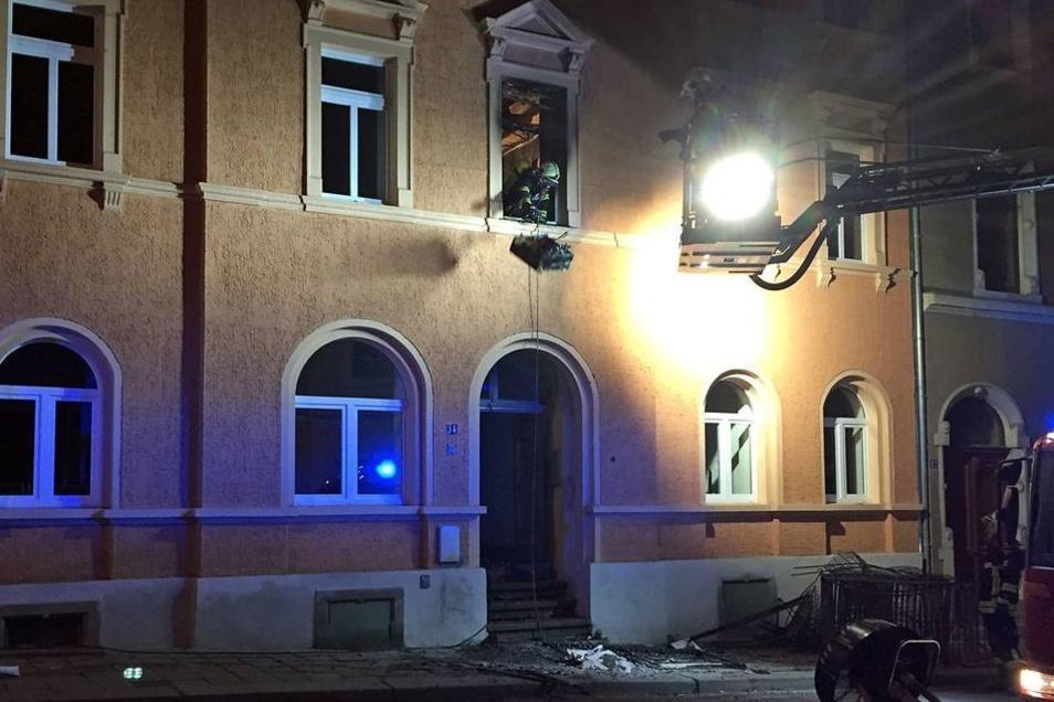 Ein Feuerwehrmann wirft verkohlte Trümmer aus dem Fenster.