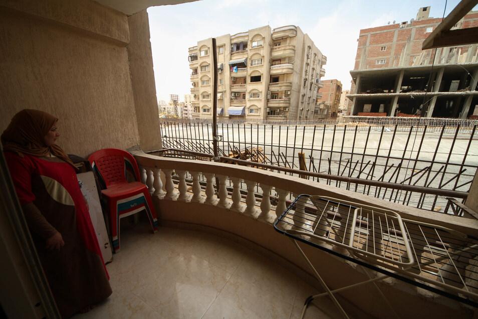 Eine Frau steht in Giseh auf dem Balkon ihrer Wohnung und blickt auf einen neu errichteten Brückenabschnitt der direkt an Wohnhäusern im Bezirk Al Omraniya vorbei führt.