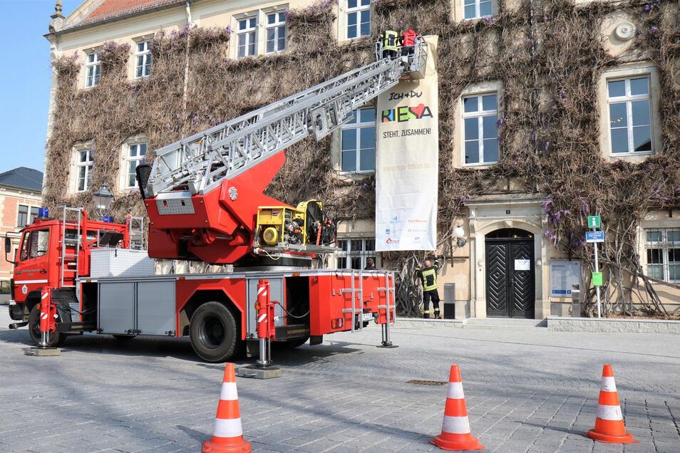 Da hilft die Drehleiter: Am Riesaer Rathaus sendet seit Donnerstag ein Plakat eine positive Botschaft aus.