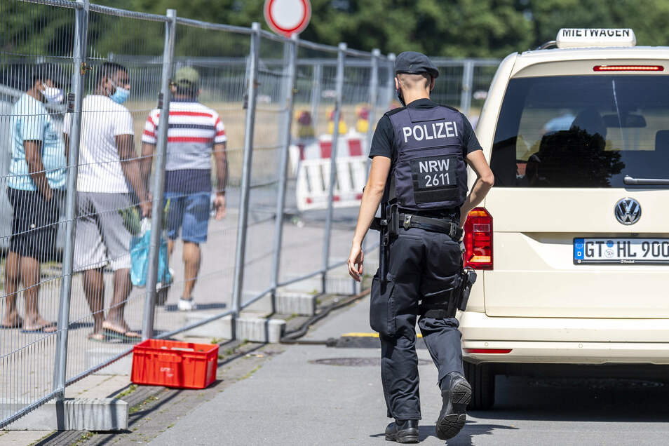 Ein Polizist geht zu einer Gruppe von Menschen, die hinter einem Bauzaun in der Stadt Verl unter Quarantäne stehen.