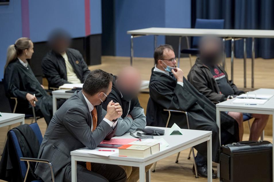 Drei von sechs Männern, die als Mitläufer der mutmaßlichen rechtsterrositischen Gruppe Chemnitz angeklagt sind, sitzen im Saal der Musikschule Chemnitz zu Prozessbeginn neben ihren Verteidigern.