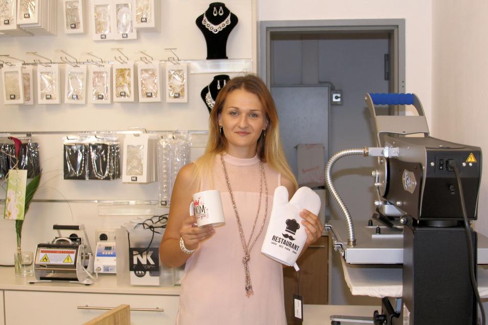 Natalie Kraft in ihrem neuen Laden in der Elbgalerie Riesa. Hier kann sie unter anderem Tassen bedrucken (kleines Gerät hinten links) oder mit der Presse rechts Schriftzüge einprägen.