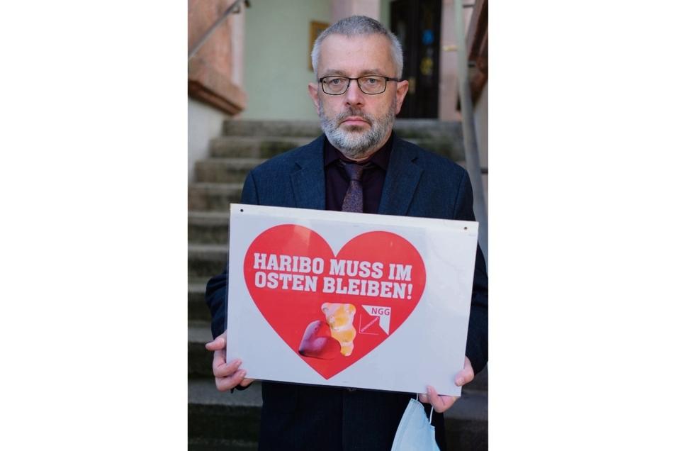 """Stefan Feustel (CDU), Bürgermeister von Wilkau-Haßlau, hält ein Schild mit der Aufschrift """"Haribo muss im Osten bleiben!""""."""