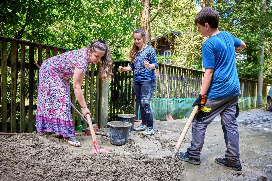 Fleißige Helfer: Amina, ihre Schwester Selma sowie Tobias (v.l.) schaufeln den Beton in die Transporteimer.