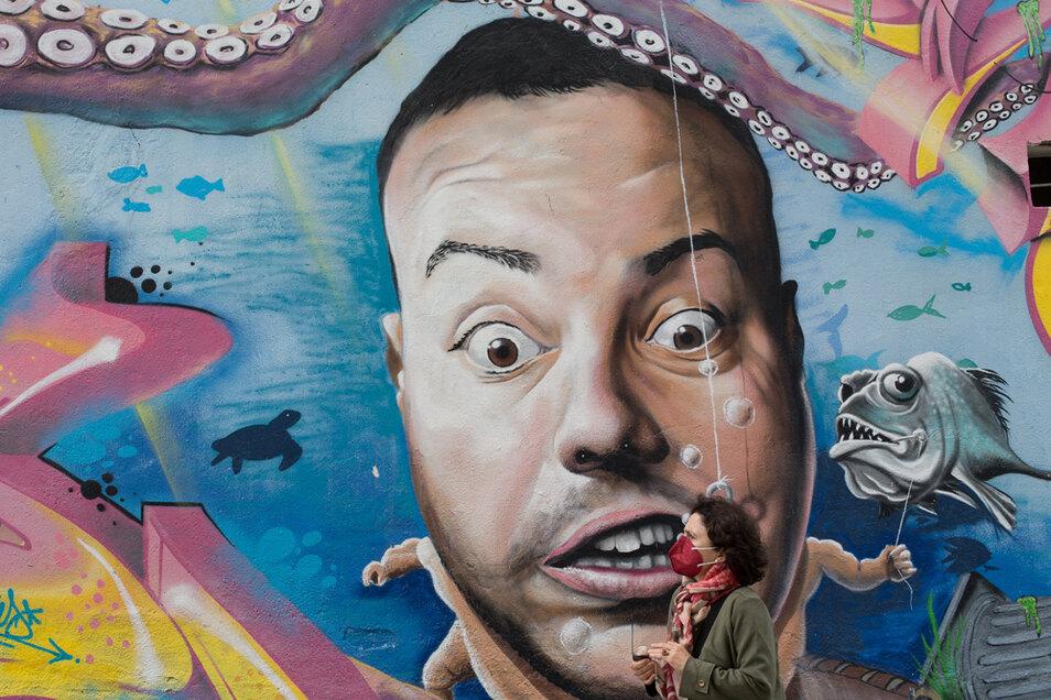 Eine Frau mit Mund-Nasen-Bedeckung geht an einem der Graffiti von Diego As im spanischen Lugo vorbei.
