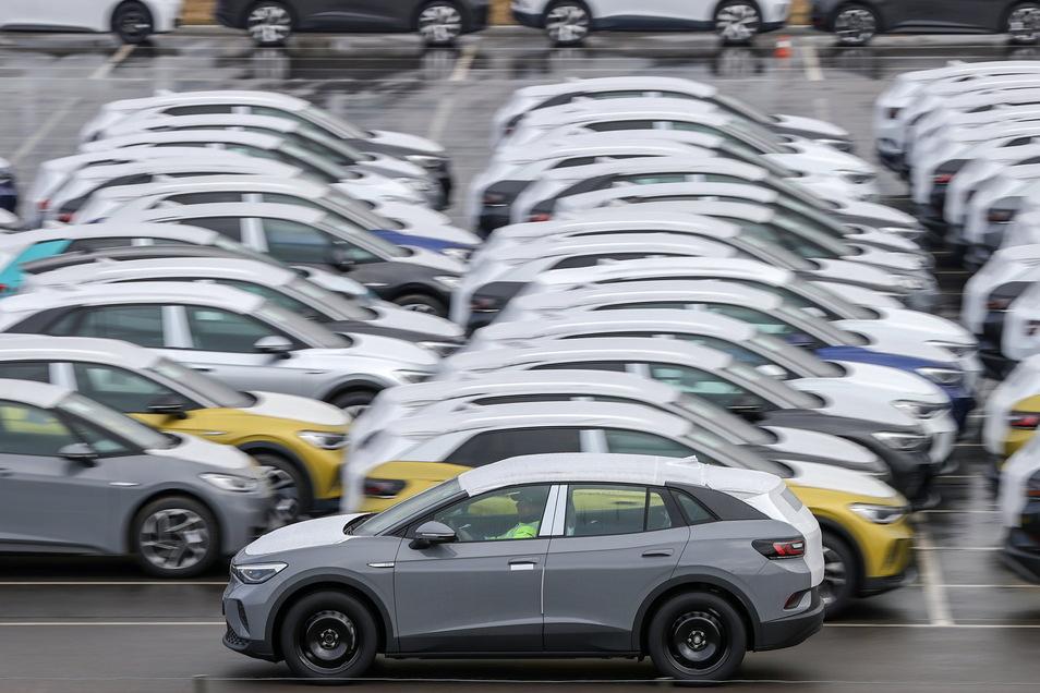 Ein Volkswagen fährt zur Auslieferung über einen Parkplatz mit weiteren Neuwagen.