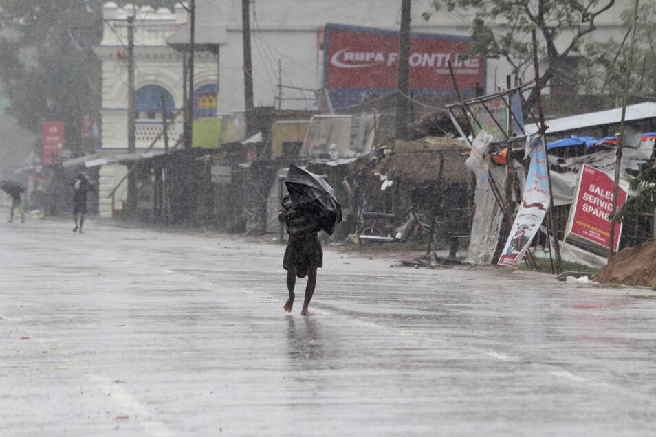 Ein Passant im indischen Chandbali schützt sich mit einem Regenschirm vor den Wassermassen.