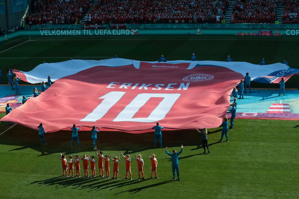 Ein riesiges Trikot zu Ehren des dänischen Spielers Christian Eriksen wird vor dem Spiel auf den Rasen gebracht.