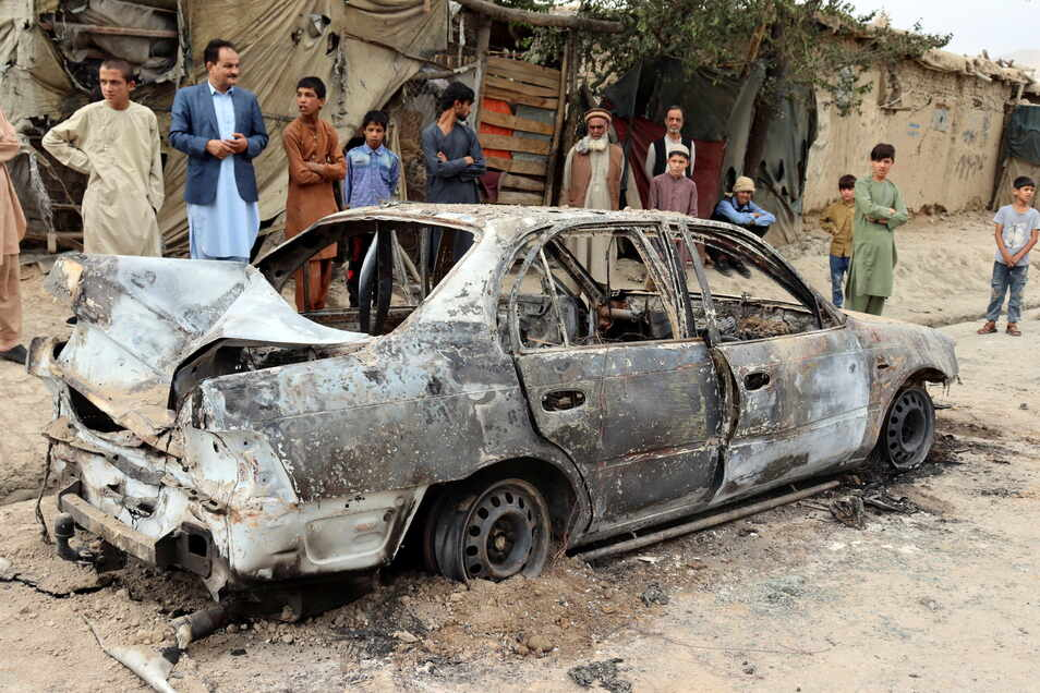 Anwohner betrachten ein durch einen Raketenangriff beschädigtes Fahrzeug.