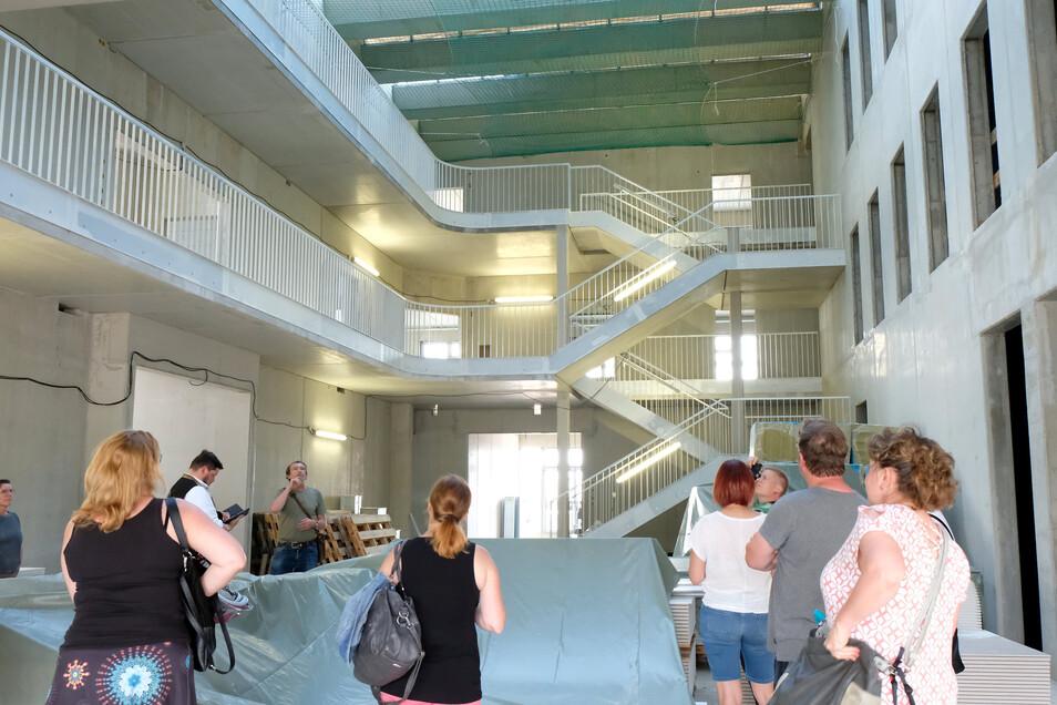 Eltern und Lehrer besichtigen das neue Gebäude ihrer im Bau befindlichen Oberschule in Klipphausen. Beim Betreten gelangt man direkt in einen Lichthof.