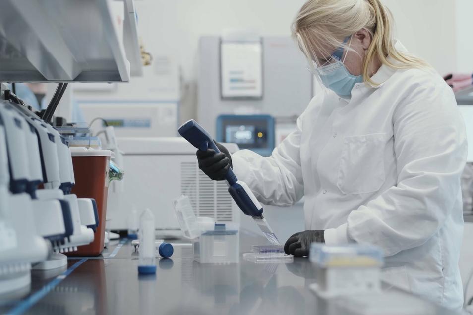 Das Videostandbild zeigt eine Mitarbeiterin des US-Konzerns Moderna bei der Herstellung eines Corona-Impfstoffs. Moderna will als erstes Unternehmen die Impf-Zulassung in der EU beantragen. Im Landkreis Meißen gibt es insgesamt knapp 3.000 Corona-Fälle.