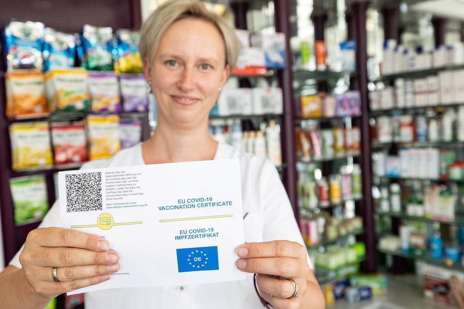 Vom gelben Impfausweis-Papier zum weißen und dann ins Handy: Sina Lindemann zeigt ein solches Zertifikat, dass dann abgerufen und gespeichert werden kann.