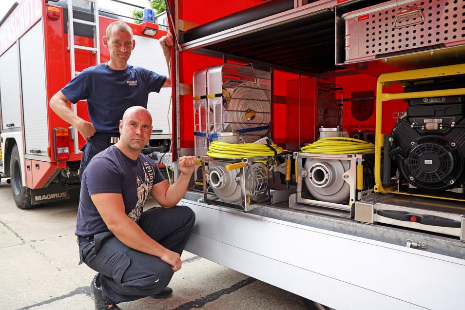 Maik Wiegner (oben) und Robert Tilke von der Feuerwehr Meißen zeigen zwei der vier Chiemsee-Pumpen, die sich auf jedem Hochwasser-Anhänger befinden.