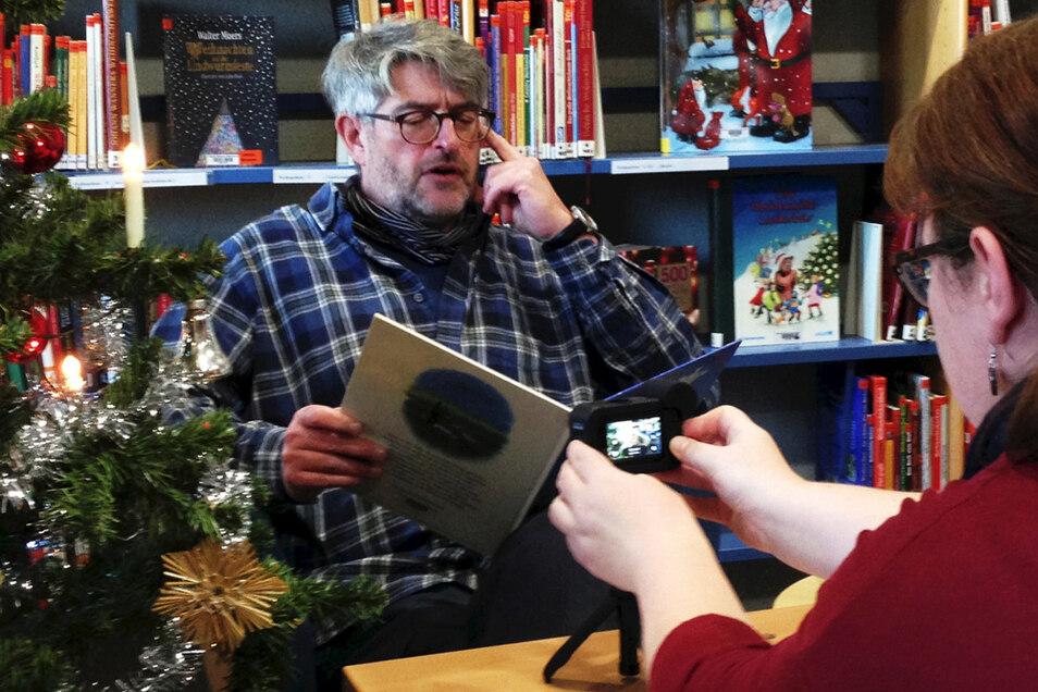 """Dietmar Michaelsen (57) liest in der Brigitte-Reimann-Stadtbibliothek Hoyerswerda für den virtuellen Adventskalender eine weihnachtliche Geschichte. Presse-Arbeiterin Susann Keck """"dreht"""" das Video, das auf Facebook und Youtube eingestellt werden wird"""