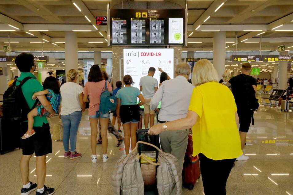 Menschen informieren sich im Abflugbereich des Flughafens von Palma de Mallorca über Corona-Regeln.