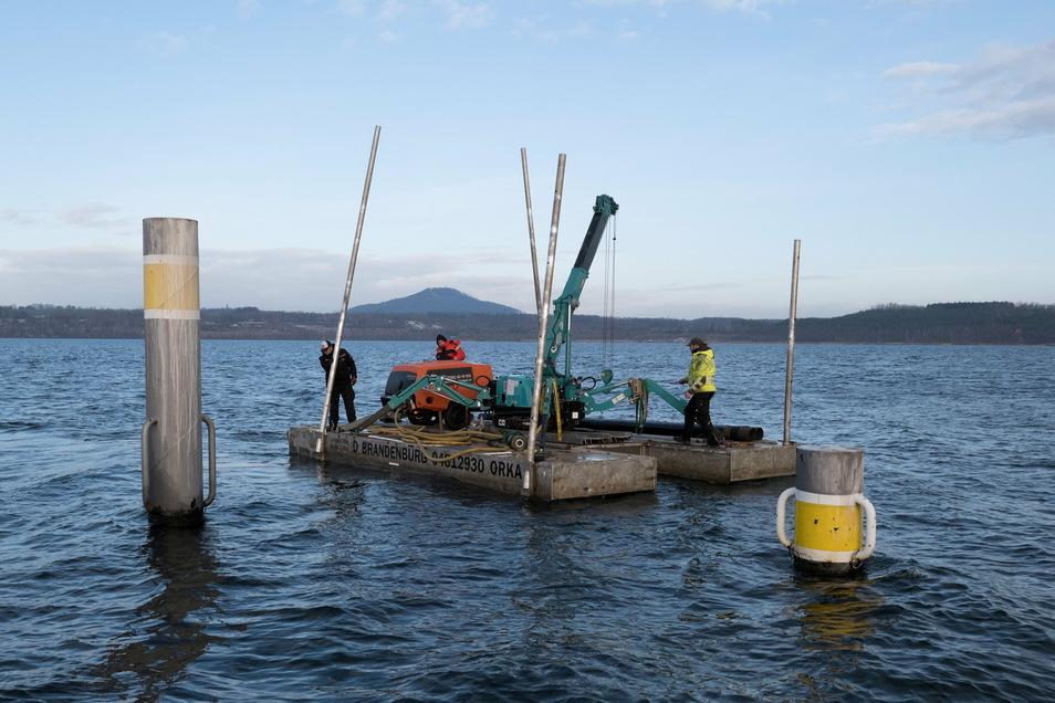 Das Team der Firma Orka Steganlagen ist mit der Arbeitsplattform auf dem Berzdorfer See. Es rammt Rohre in den Seeboden - bei Wind und Wetter.