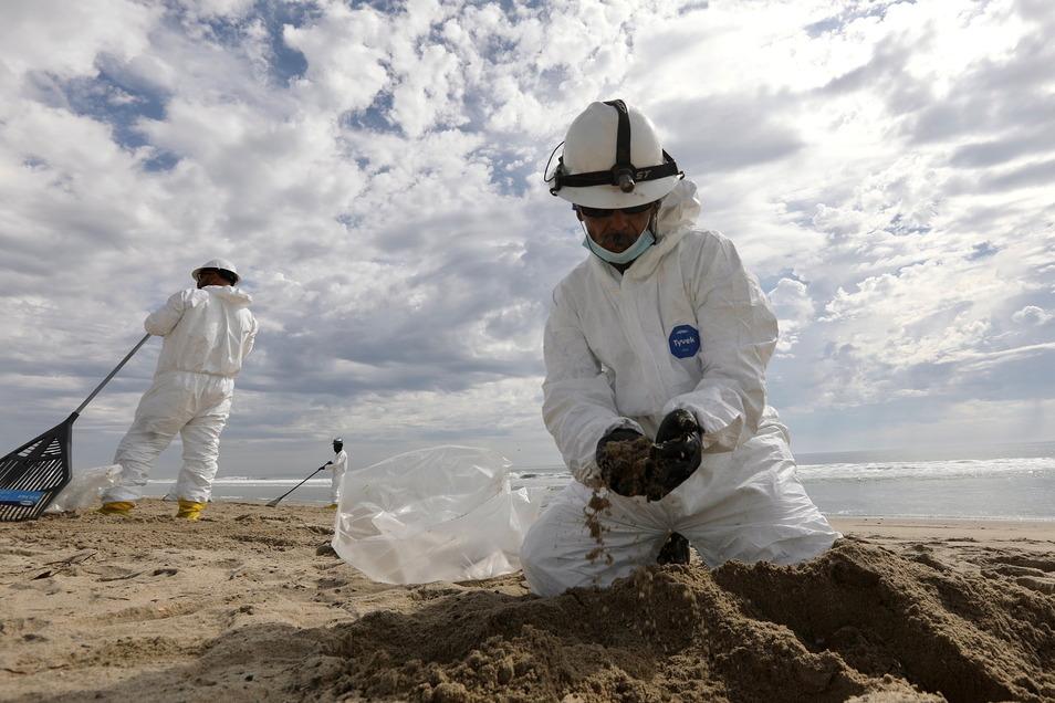 Mitglieder des Aufräumteams sammeln am Huntington Beach in Orange County, Kalifornien, Öl aus dem Sand.