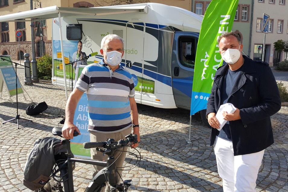 Frank Weide (links) aus Rudelsdorf ist mit seinem E-Bike zum Waldheimer Markt geradelt und unterhält sich mit Silvio Zschage vom MDR über den Radweg.