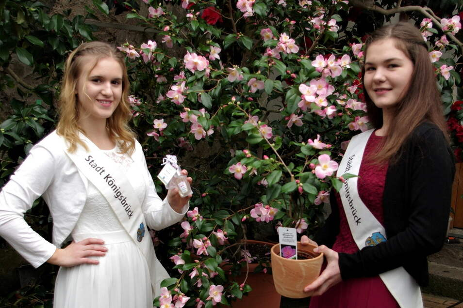 Die Kameliendamen Franziska (l.) und Lilly präsentieren das Kamelienparfüm und eine Pflanze, die man erwerben kann.