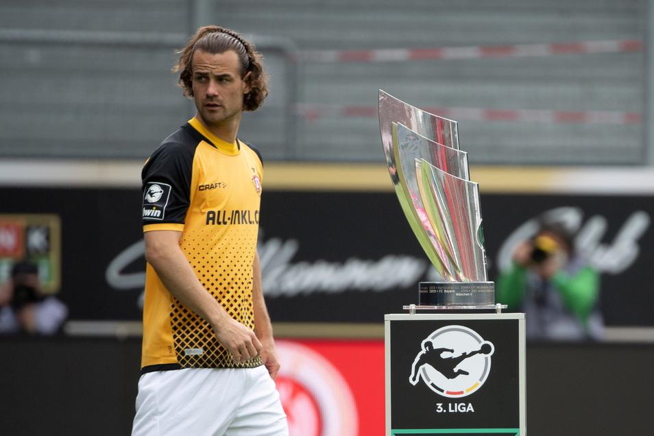 Kapitän Yannick Stark geht vor dem Anpfiff am Meisterpokal der 3. Liga vorbei, nach dem Spiel will er den in die Höhe recken. Allerdings ist es nur ein Duplikat, das Original steht in Rostock.