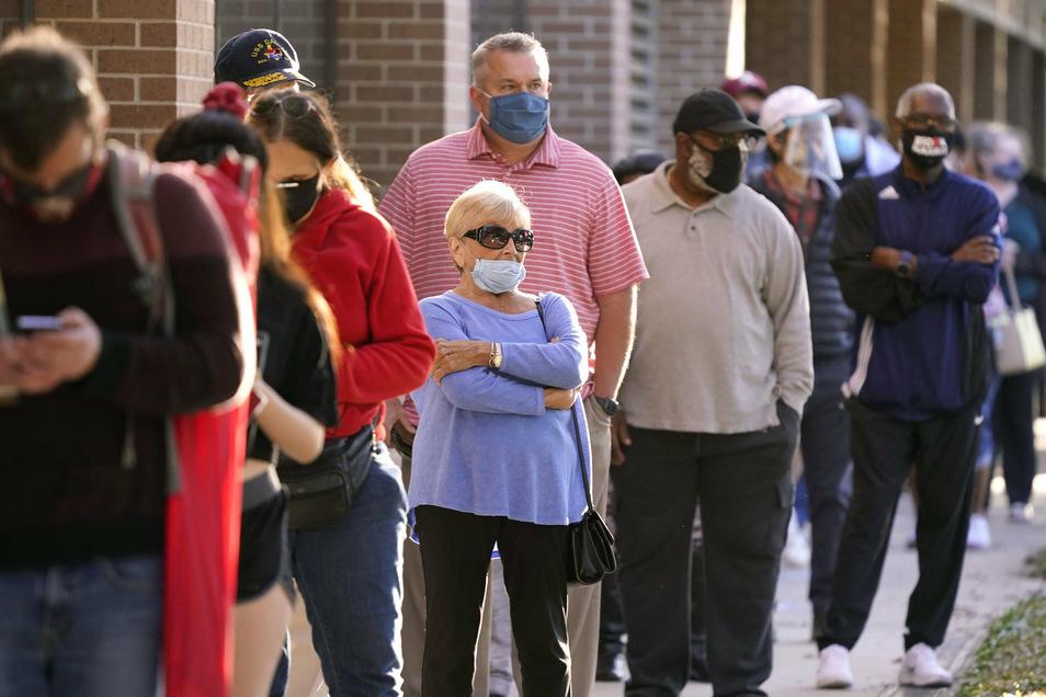 Wähler warten in einer Schlange vor dem Rathaus um vorzeitig ihre Wahlstimme abzugeben.