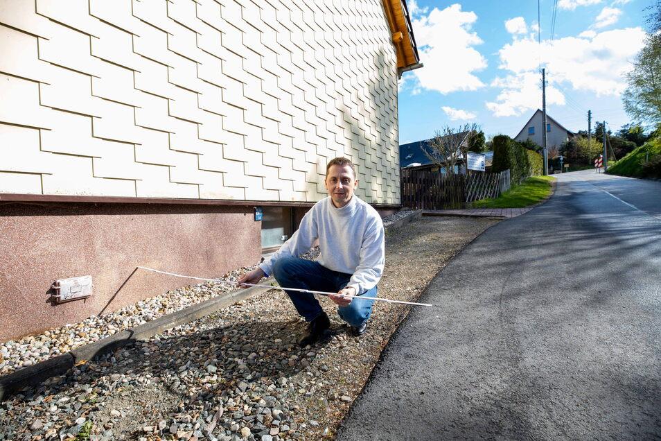 Marco Eißer zeigt mit dem Zollstock, dass die Glasfaserleitung der Telekom nur drei Meter von seinem Grundstück vorbeiläuft.