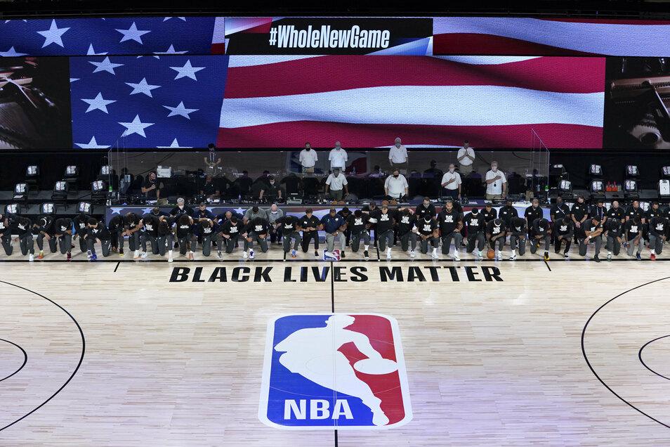 """Die Spieler der New Orleans Pelicans und von Utah Jazz knien beim Abspielen der Nationalhymne vor einem """"Black Lives Matter""""-Schriftzug."""