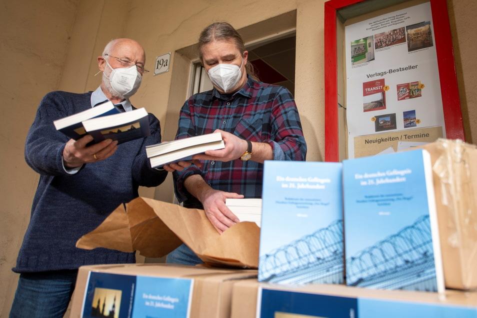 Der Verleger Jens Kuhbandner (r.) und der Autor Ulfrid Kleinert packen das im Notschriftenverlag erscheinende Buch über die Dresdner Justizvollzugsanstalt am Hammerweg aus.